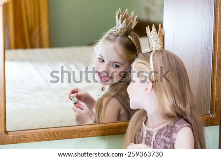 The little princess looks in the mirror - stock photo