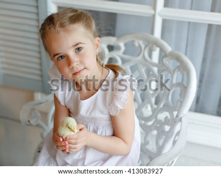 The little red-haired girl with pigtails holding a yellow chick, on a light background