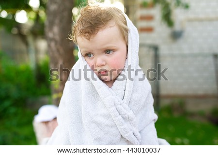 The little sad girl is wrapped up in a white towel.