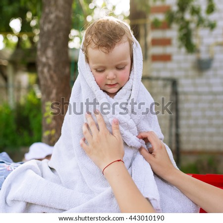 The little sad girl is wrapped up in a white towel. - stock photo