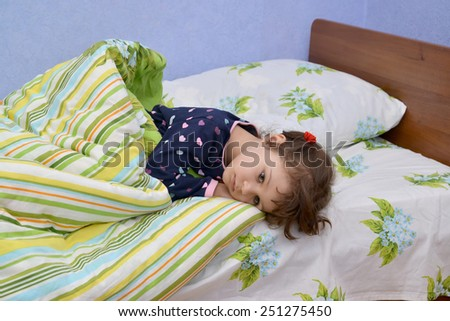 The little sad sick girl lies in a bed - stock photo