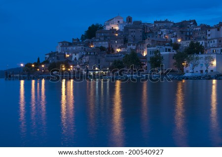 The little town of Anguillara Sabazia on Bracciano's Lake in Italy, shot at dusk with reflections on the lake and a blue sky.