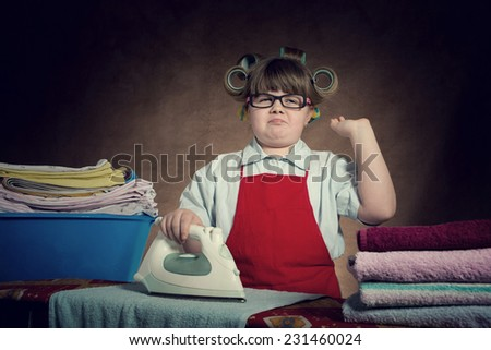 the little wife diligently irons, you are very tired. vintage-looking/the little wife diligently irons - stock photo
