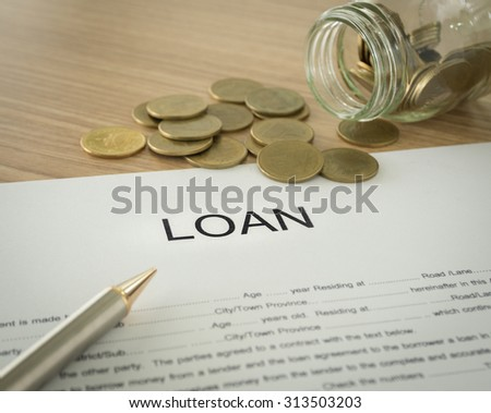 The loans documents and gold coin on desk's bankers.