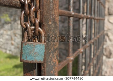 The lock on the chain. Old rusty chain with a lock on the iron gate. Symbol imprisonment and slavery. Property security chain. Closed iron gate with a lock. - stock photo