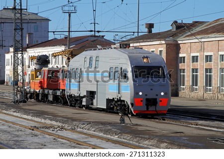 The locomotive is on the tracks near the railway station