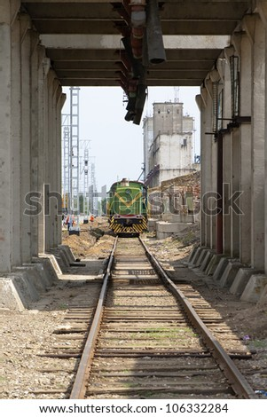 The locomotive is on the tracks near the station and the loading rack - stock photo