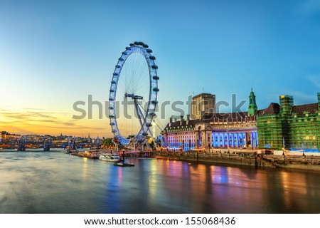 The London Eye on the South Bank of the River Thames at night in London, England.