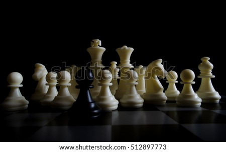 The loneliness of the black pawn, isolated among white chessmen on a metallic chessboard and a black background