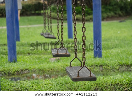 The loneliness swings in the park after rain.