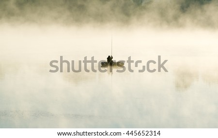 The lonely fisherman by the boat in fog - stock photo