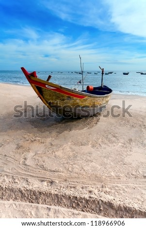 the lonely fishing boat on sand, in the evening