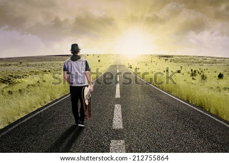 The lonely guitarist walking on road, shot outdoors at dusk
