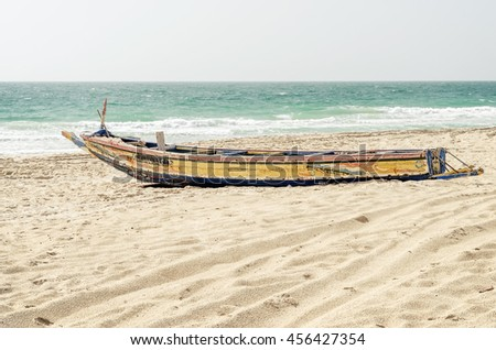 The lonely old boat with peeling paint on a sandy beach in Mauritania, Africa - stock photo