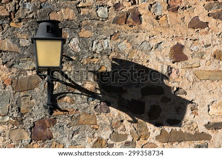 The long afternoon shadow of a lamp post of a street light against an old castle wall in Spain - stock photo
