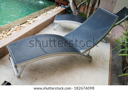 The long chairs set by swimming pool