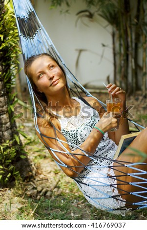 The long hair thoughtful girl in white openwork dress sits down in the hammock and drinks orange beverege.