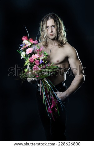The long-haired male fitness model shirtless holding a bouquet of flowers. black background - stock photo