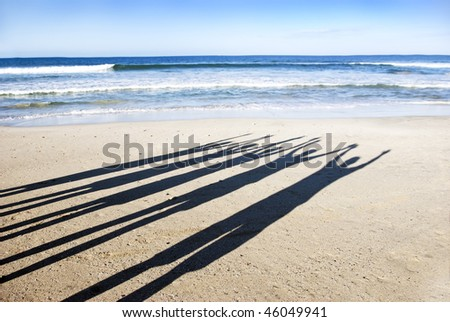 The long silhouette shadows of five people on the beach in late afternoon sun - stock photo