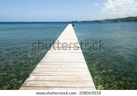 The long wooden pier for tourists to swim on Roatan island (Honduras). - stock photo