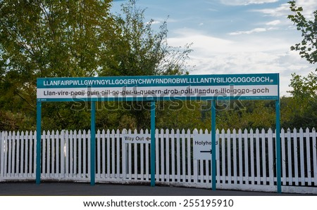 The longest place name of the UK, Llanfairpwllgwyngyll, on the platform of the railway station in the town - stock photo