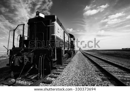 The looming front and side of a vintage train engine beside a railway track leading to a distant grain storage elevator - stock photo