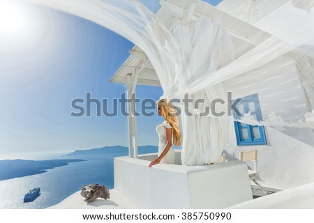 The lovely young couple beautiful romance sexy shapely woman in a beautiful Greek landscape amazing view in Santorini Island Santorini Greece in wedding dress and veil is romantic and beautifully - stock photo