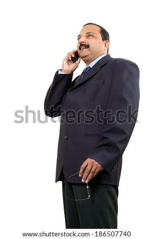 The low angle photograph of an  Indian businessman using cell phone .