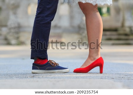 The lower legs of a woman and a man standing opposite each other - red is the unifying color - stock photo