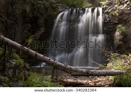 The lower portion of Twin Falls waterfall in Glacier National Park. Taken with a long exposure, the water shows the patterns formed as it falls across the rocks.