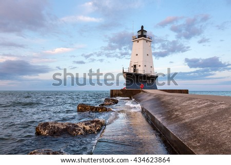 The Ludington North Breakwater Pier Lighthouse rises above Lake Michigan with an early morning sky.  - stock photo