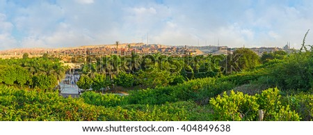 The lush greenery of Al-Azhar park with the dusty slums of Garbage City on the background, Cairo, Egypt. - stock photo