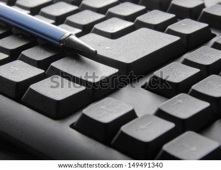 the luxury black pen on computer keyboard  - stock photo