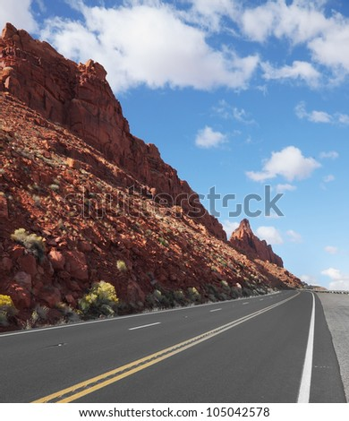 The magnificent marked American road passes between rocks of red sandstone - stock photo