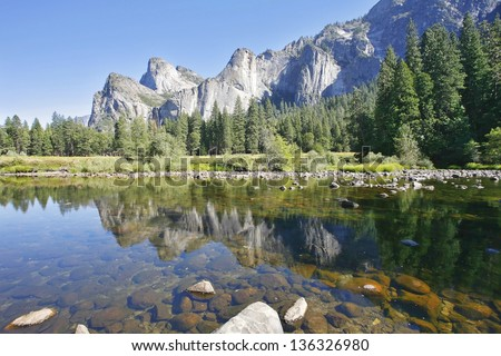 The magnificent Yosemite Valley. Three scenic rocky peaks and reflected in the smooth waters of the Merced - stock photo