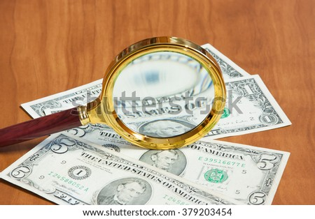 The magnifier in the gilt frame lays on dollars