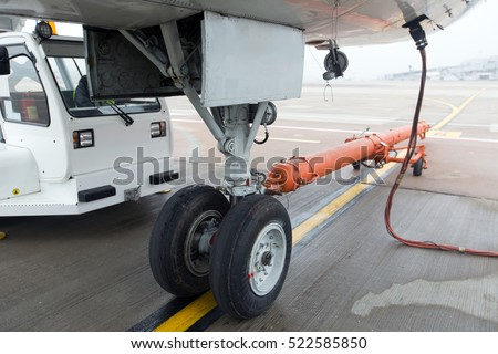 The main landing gear of the passenger jet airplane close up. The plane is parked on the airport apron. Chassis hitched with a carrier for the towing aircraft.