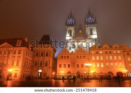 The main square with tourists and the Gothic building of the Church of Our Lady before Tyn in foggy night, Prague Old Town, Czech Republic - stock photo
