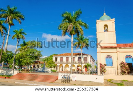The main street of the Cuban town with a beautiful church in the background, Vinales, Cuba - stock photo