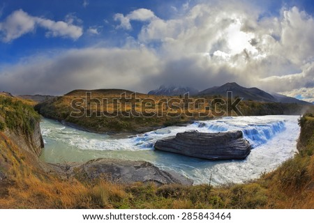 The majestic cascading waterfall - Cascades Paine. National Park Torres del Paine in southern Chile, in Patagonia. Billowing clouds covered the setting sun - stock photo