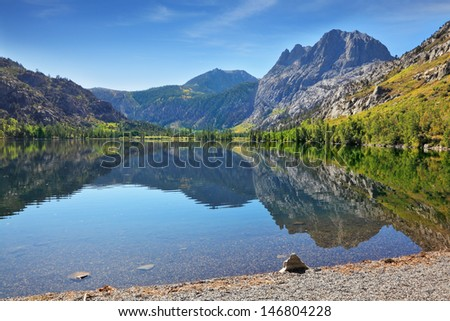 The majestic mountains and pine forests are reflected in the smooth water. A quiet lake in the mountains of California.