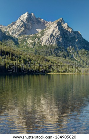The majestic Sawtooth mountains reflected in Redfish Lake in central Idaho - stock photo