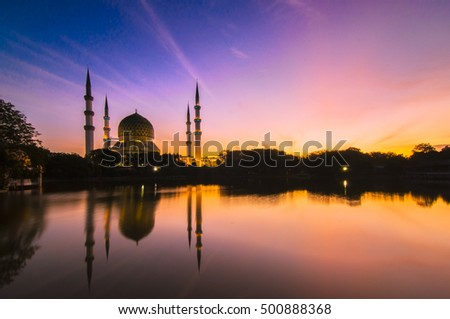 the majestic sunrise at the lake with mosque as point of interest. long exposure shot cause motion to the sky and calm water reflection. vibrant color, nature composition and soft focus.