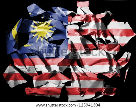 The Malaysia flag  painted on pieces of torn paper on black background - stock photo