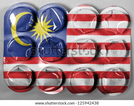 The Malaysia flag  painted on tablets or pills - stock photo