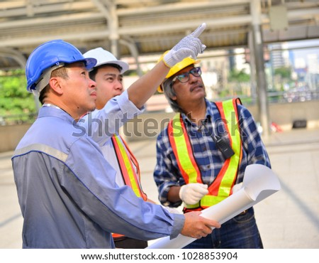 The male engineer is checking the blueprint and instructs the project leader to accomplish the goal