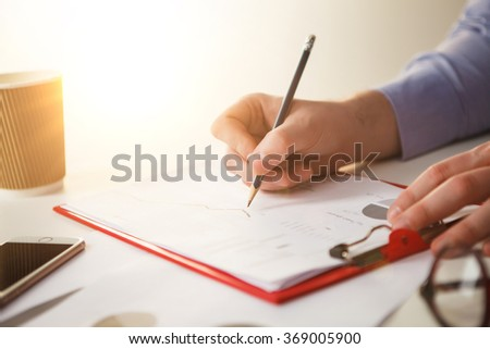The male hand drawing a graph of growth against the background of the table