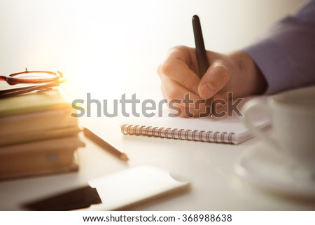 The male hand with a pen and the cup of coffee and notebook