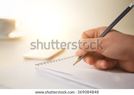 The male hand with a pencil and the cup of coffee and notebook on the table