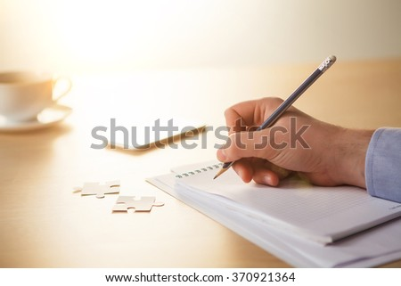 The male hands with a pencil and the cup